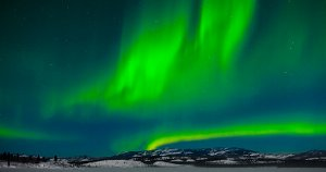 Excited oxygen atoms emit green light - the Aurora Borealis/Northern Lights.