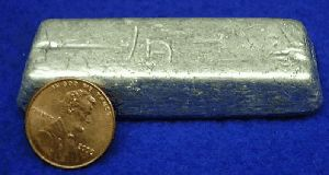 A bar of indium metal and a penny.
